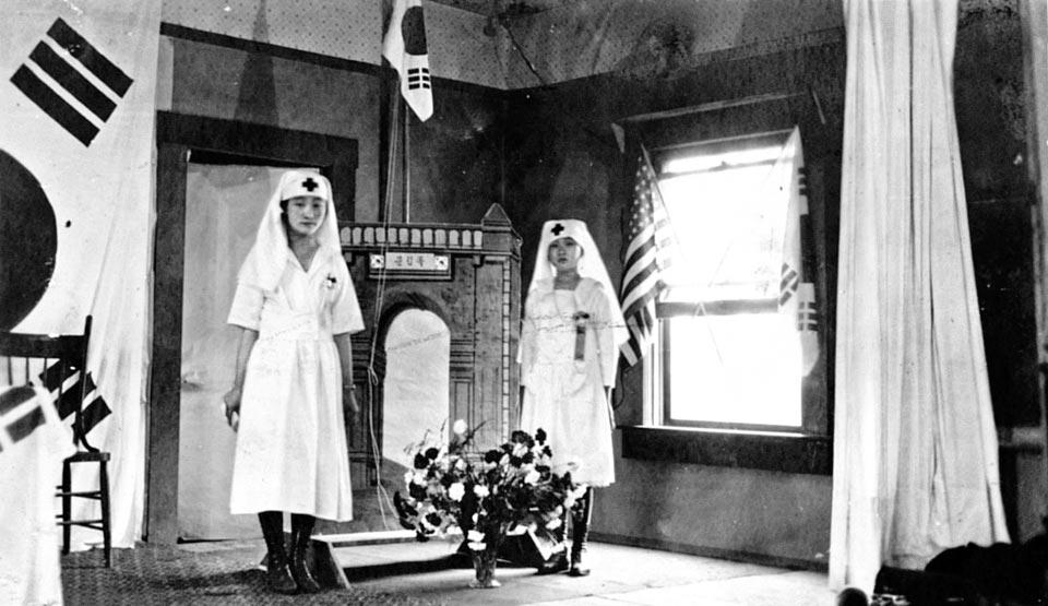1920년 3·1운동 1주년을 맞아 미국 디누바에서 한인 여성들이 적십자 소속 간호사 복장으로 독립문 모형 앞에서 촬영한 사진.
