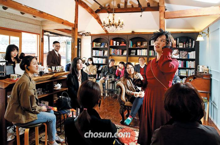 시간 여행을 안내하는 '광주 100년의 이야기' 버스의 가이드이자 배우, 가수이기도 한 '나비'역의 배우가 양림쌀롱에서 연기 중이다.