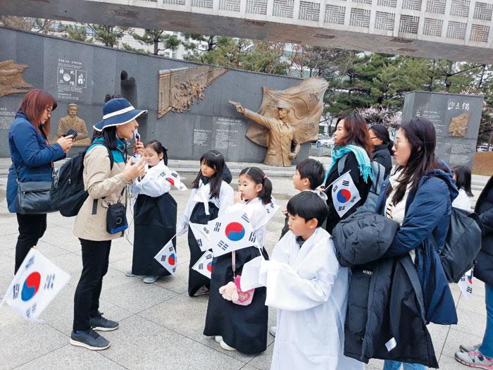 안중근공원에서 태극기를 들고 해설사의 설명을 듣고 있는 부천시티투어 참가자들.