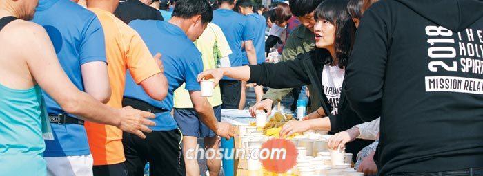 2018년 서울하프마라톤에서 자원봉사자들이 주자들에게 생수를 나눠주는 모습.