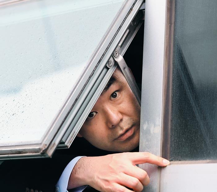 25일 자유한국당 의원들이 바른미래당 채이배 의원실 입구를 봉쇄하자 채 의원이 '불법 감금 당했다'며 창문 밖으로 고개를 내밀어 기자들과 얘기하고 있다.