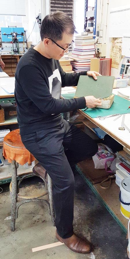 책 제본 분야 프랑스 국가 공인 명장(MOF)으로 선정된 조용덕씨가 파리 13구에 있는 자신의 공방에서 낡은 책의 표지를 떼어내 손질하고 있다.