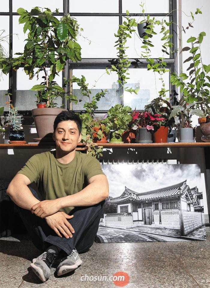 """서울 을지로 '어번디테일'에서 만난 다니엘 텐들러 소장은 """"한옥을 지을 땐 내가 독일인이라고 생각하지 않는다""""고 했다. 곁의 사진은 이상훈 작가가 촬영한 은평한옥 외관."""