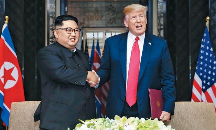 도널드 트럼프(오른쪽) 미국 대통령과 김정은 북한 국무위원장이 작년 6월 12일 싱가포르 카펠라호텔에서 공동성명에 서명한 뒤 악수하고 있다.