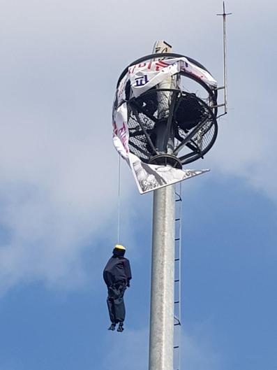 """12일 오전 대구 남구 영대병원네거리 교통관제 폐쇄회로(CC)TV 타워에 한 남성이 사람 모양의 인형과 """"수술받게 해 달라""""는 내용의 현수막을 내건 채 시위를 하고 있다. /대구 남부경찰서 제공"""