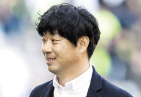 K리그 경기에서 선수들을 바라보며 흐뭇하게 웃고 있는 김병수 강원 감독.