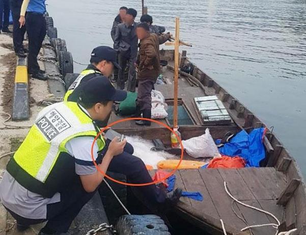 지난 15일 소형 목재 선박을 이용해 강원도 삼척항에 도착한 북한 선원들이 배를 정박한 채 대기하고 있다. 붉은 원 안에 있는 것이 그물이다./김경현씨 제공