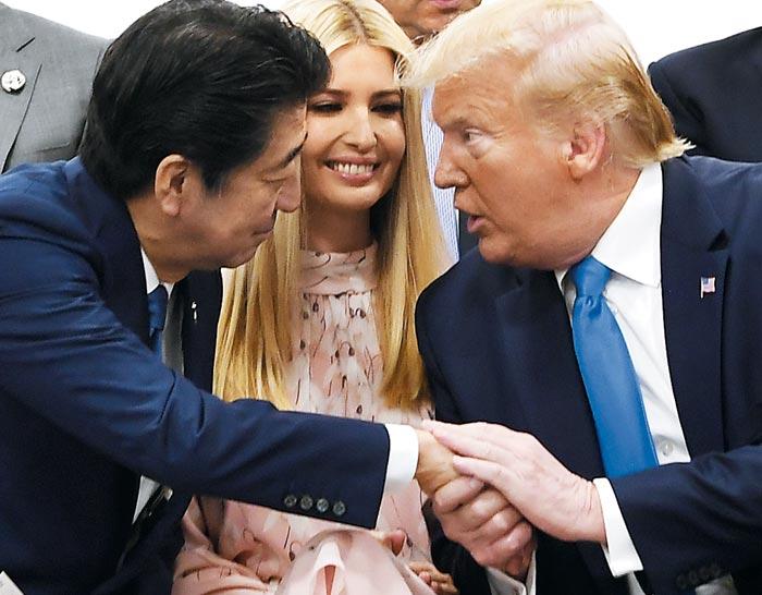 지난달 29일 일본 오사카에서 열린 주요 20국(G20) 정상회담의 특별 세션에서 도널드 트럼프(오른쪽) 미 대통령과 아베 신조(왼쪽) 일본 총리가 이방카 트럼프(가운데)를 사이에 두고 손을 붙잡고 이야기하고 있다.