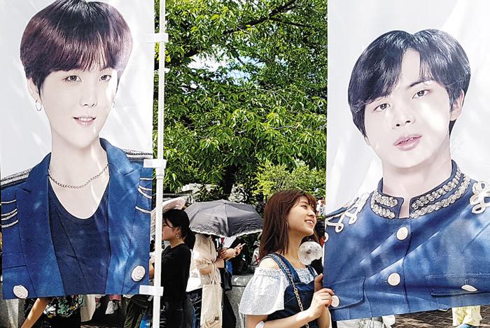 6일 방탄소년단(BTS) 콘서트가 열린 일본 오사카 '얀마 스타디움 나가이'에서 한 일본 팬이 BTS 멤버의 대형 사진 앞에서 기념 촬영을 하고 있다.