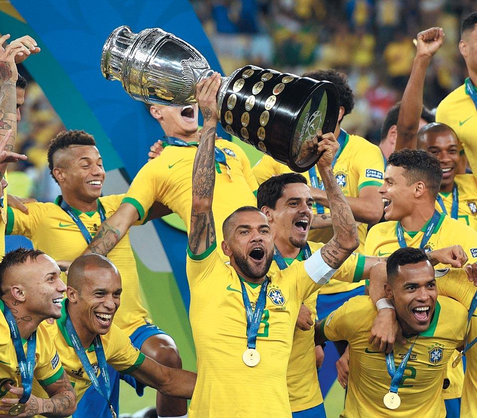 브라질 축구대표팀 주장 다니 알베스(가운데)가 8일 자국 리우데자네이루 마라카낭 스타디움에서 페루와 벌인 2019 코파 아메리카 결승전에서 3대1로 승리한 뒤 우승컵을 들고 동료들과 함께 환호하는 모습.
