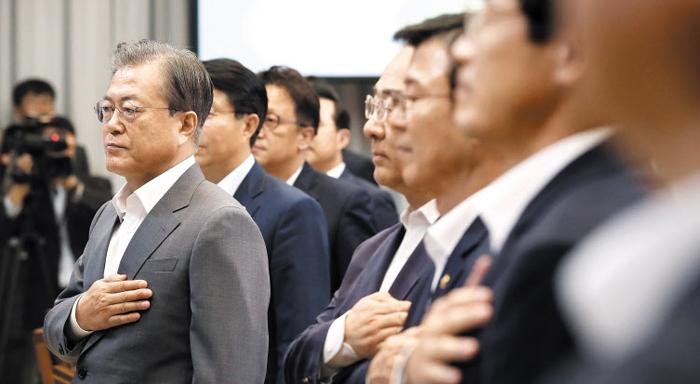 문재인 대통령이 9일 청와대에서 열린 '공정경제 성과 보고 회의'에서 참석자들과 함께 국기에 경례하고 있다.