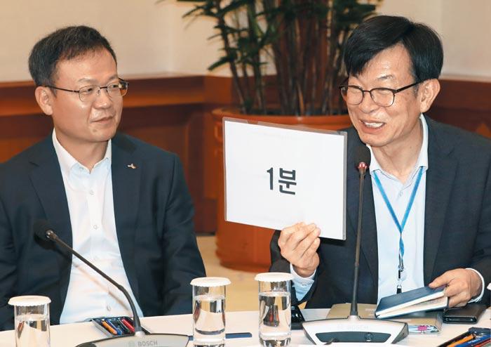 김상조(오른쪽) 청와대 정책실장이 10일 청와대 간담회에서 기업인들에게 발언 시간을 지켜 달라며 '1분' 남았다는 팻말을 들고 있다.