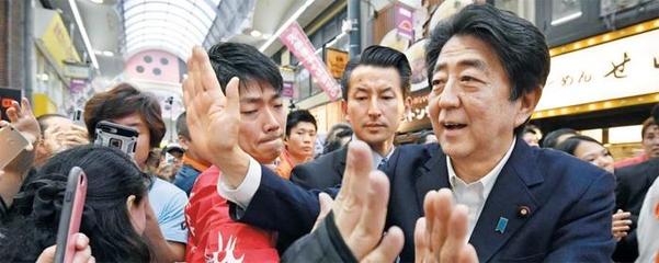 참의원 선거 유세에 나선 아베 신조(安倍晋三·오른쪽) 일본 총리가 6일 오사카(大阪)의 한 상점가에서 유권자들에게 둘러싸여 손을 흔들고 있다. /연합뉴스