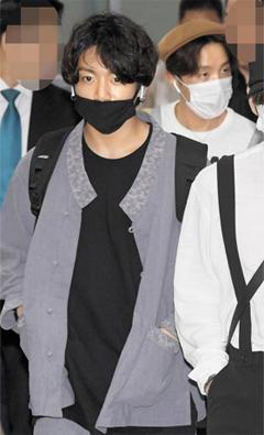 인기 아이돌 그룹 방탄소년단(BTS) 멤버 정국(가운데)이 지난 8일 오후 회색 톤의 생활 한복을 입고 김포국제공항을 통해 입국하고 있다.