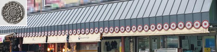 경기 수원시 미나리시장 점포와 그 위에 설치된 차광막. 수원시에는 최근 이 차광막에 붙은 꽃잎 모양의 장식물을 모조리 교체해 달라는 민원이 들어왔다. 일본 왕실을 상징하는 국화꽃 문장(紋章)과 모양이 닮았다는 이유에서다. 수원시는 이 장식물이 통일신라의 꽃무늬 전통 기와(왼쪽 위 사진)를 본떠 만든 것이라는 입장이다.