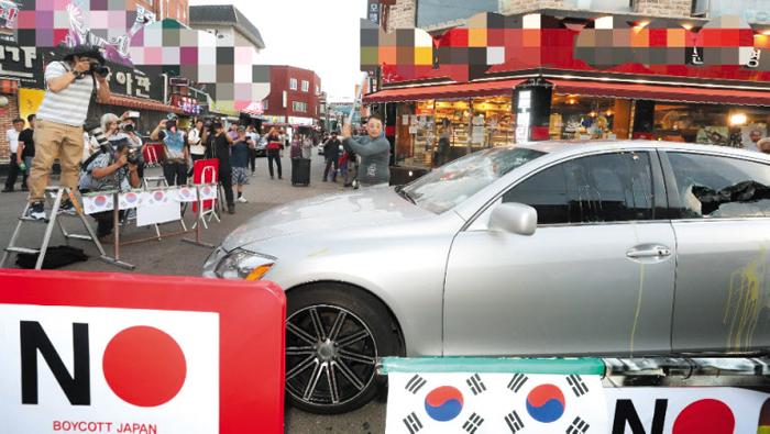"""23일 오후 인천 남동구 구월동에서 한 상인(가운데)이 자신의 은색 렉서스 차량을 쇠파이프로 부수고 있다. 상인은 """"일본에 강한 불매운동 의지를 보여줄 필요가 있다고 생각했다""""고 밝혔다."""