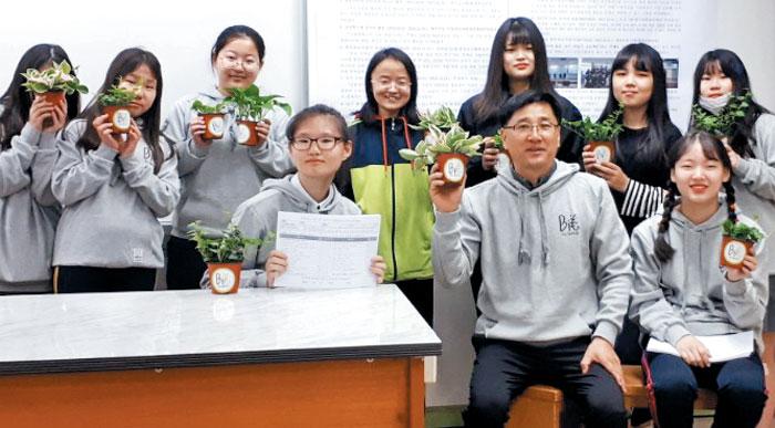지난해 10월 인천 부평구 부일여자중학교에서 환경 동아리 '빅 사이언스' 학생들과 구교정(앞줄 오른쪽에서 둘째) 교사가 공기 정화식물을 들어 보이고 있다