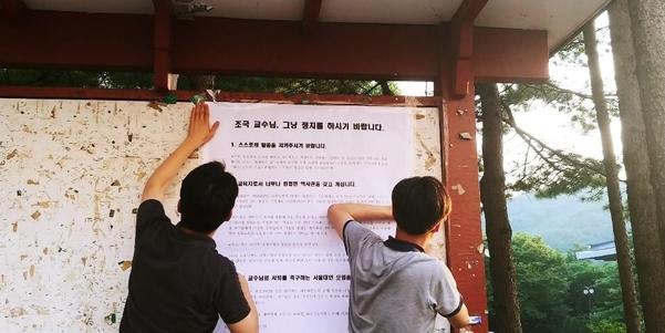 서울대 트루스 포럼 소속 학생들이 학내 게시판에 '조국 교수님, 그냥 정치를 하시기 바랍니다'라는 제목의 대자보를 붙이고 있다./서울대 트루스 포럼 페이스북