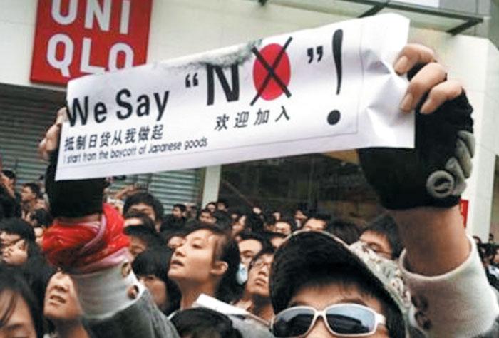 게시물 사진 속 반일 시위대는 'NO'라는 글자에서 알파벳 'O'를 붉은색으로 칠해 일장기를 연상케 하는 플래카드를 들었다.