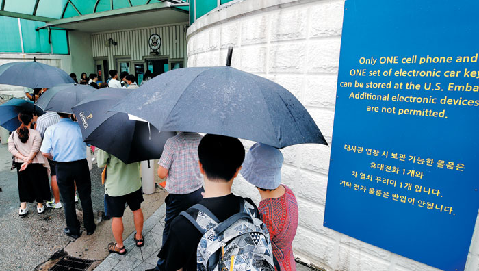 미국이 '방북자 무비자 입국 제한' 조치를 시행한 다음 날인 7일 서울 종로구 주한 미 대사관 영사과 앞에 비자를 신청하려는 사람들이 우산을 쓰고 줄 서 있다.