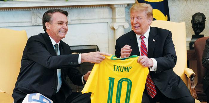 도널드 트럼프(오른쪽) 미국 대통령과 자이르 보우소나루 브라질 대통령이 지난 3월 백악관에서 정상회담을 하기 전 자국 축구 국가대표팀 유니폼을 교환하고 있다. / 블룸버그