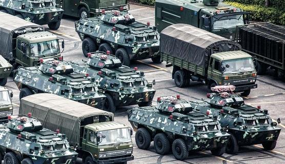 중국 인민해방군 산하 무장경찰의 군용 트럭과 장갑차들이 15일 홍콩 인근 도시인 중국 광둥성 선전의 한 스포츠 스타디움에 줄지어 서있다. AFP통신은 이날 '홍콩과 불과 7㎞ 떨어진 선전 스포츠 스타디움에서 중국 무장경찰 수천명이 경기장 내부에 장갑차를 배치하고 붉은 깃발을 흔들며 훈련하는 모습이 포착됐다'고 보도했다. /로이터 연합뉴스