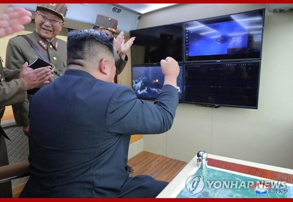 사진은 중앙통신 홈페이지에 공개된 것으로, 김 위원장이 지휘소 모니터를 보며 환호하는 모습./연합뉴스
