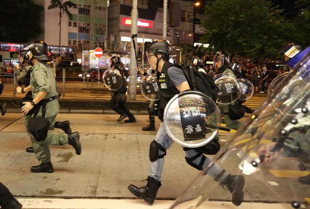 17 일 오후 (현지 시간) 홍콩 카오 룽 반도 몽콕 경찰서 인근 거리 에서 진압 경찰 이 시위대 를 쫓고 있다. / 연합 뉴스