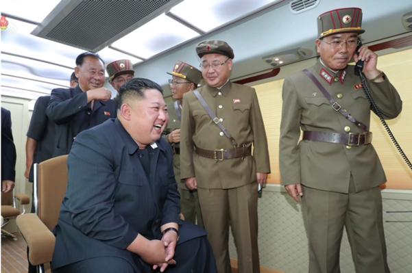 김정은 북한 국무위원장이과 수행원들이 지휘소 모니터를 바라보며 웃고 있다. /연합뉴스