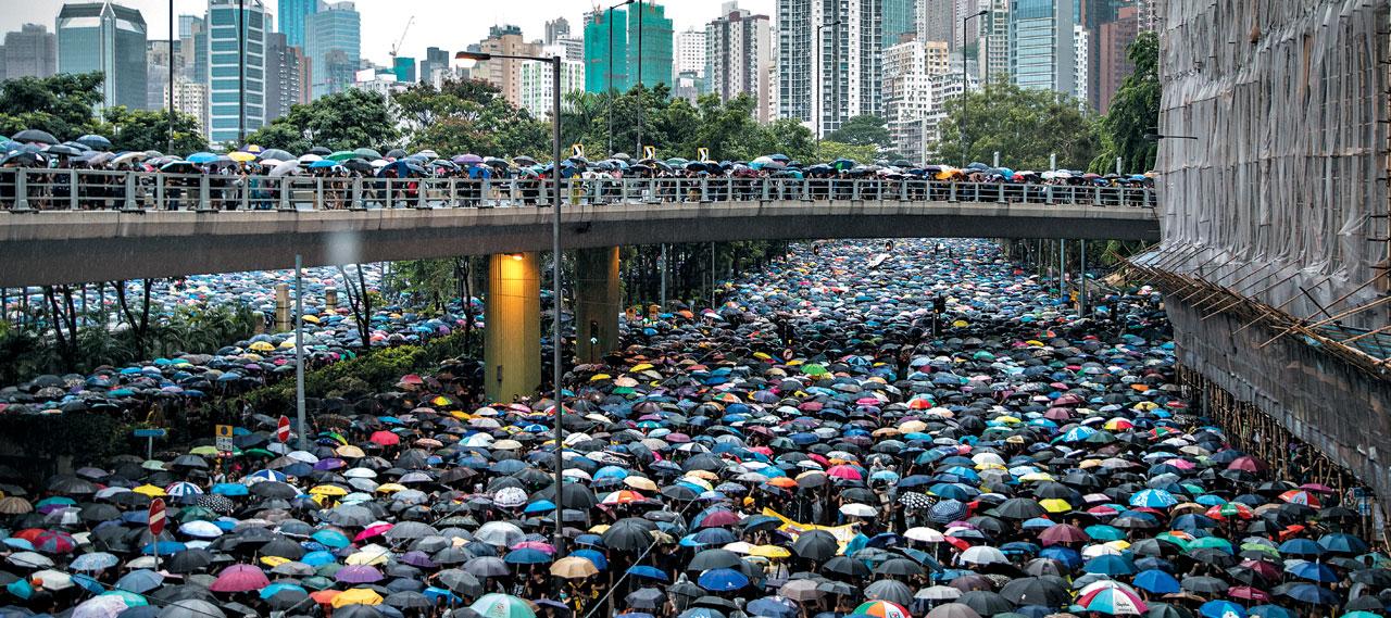 홍콩 시위 참가자들이 18일 비가 오는 가운데 우산을 펼쳐들고 홍콩 시내 도로와 육교 위를 행진하고 있다.