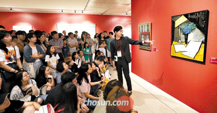 지난 15일 전시해설자 정우철씨가 관람객 100여명에게 둘러싸인 채 베르나르 뷔페의 대표작 '유언장 정물화'를 설명하고 있다.