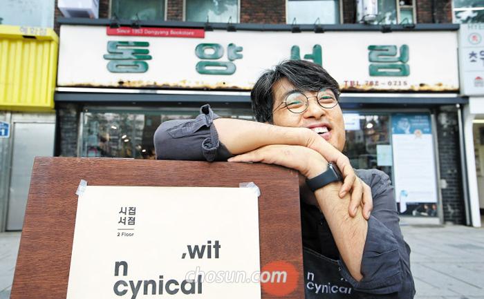 동양서림 앞에 놓인 위트앤시니컬 입간판에 기대 웃고 있는 시인 유희경.