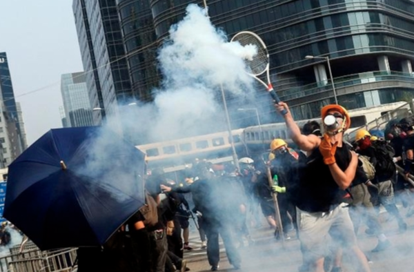 24일 홍콩 송환법 반대 시위 중 한 참가자가 경찰이 쏜 최루탄을 테니스채로 막아내고 있다./로이터 연합뉴스