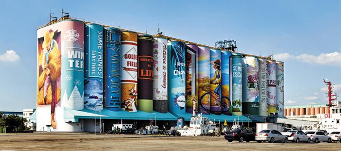 인천의 새로운 명물로 자리 잡은 내항 7부두 사일로의 벽화. 거대한 잿빛 구조물에 색을 입히고 그림을 그려 마치 도서관이나 서점의 서가처럼 보이게 했다.