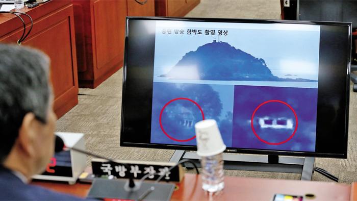 """화면에 뜬 함박도 영상 보는 국방부장관 - 정경두 국방부 장관이 4일 국회 국방위원회 전체회의에 참석해 북한의 함박도 군사 시설 관련 질의를 받고 있다. 야당 의원들은 북한의 함박도 군사 시설에 대해 """"9·19 군사 합의 위반""""이라고 했고, 정 장관은 """"합의 위반이 아니다""""라고 했다. 정 장관 앞에 놓인 TV 화면에 TV 조선의 함박도 의혹 보도 관련 영상이 띄워져 있다."""