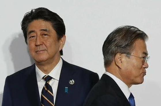 문재인(오른쪽) 대통령이 지난 6월 28일 오전 일본 오사카에서 열린 주요 20개국(G20) 정상회의 공식 환영식에서 의장국인 일본의 아베 신조 총리와 악수한 뒤 이동하고 있다. /연합뉴스