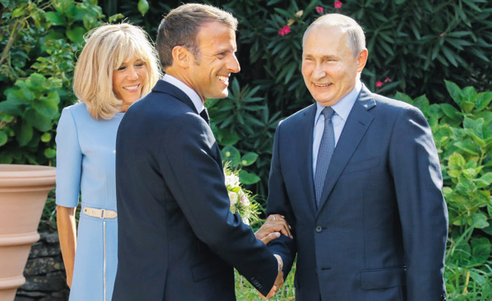 에마뉘엘 마크롱(가운데) 프랑스 대통령이 지난달 19일 대통령 여름 별장인 남부 지중해 연안 브레강송 요새에서 아내 브리지트(왼쪽) 여사와 함께 블라디미르 푸틴 러시아 대통령을 환영하고 있다.