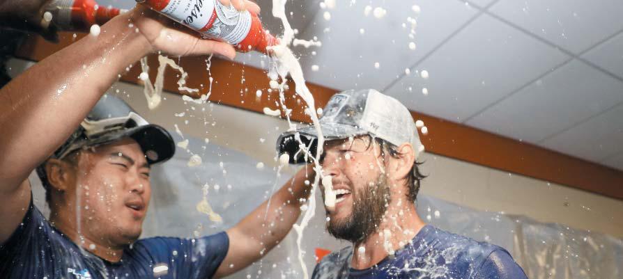 최근 부진에 빠졌던 류현진도 모처럼 활짝 웃었다. 11일 LA 다저스 투수 류현진(왼쪽)이 동료 클레이튼 커쇼에게 맥주를 뿌리며 팀의 서부지구 우승을 기뻐하는 모습.