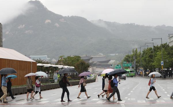 중부지방에 많은 비가 내린 10일 오전 서울 광화문광장에서 시민들이 걸어가고 있다. /연합뉴스