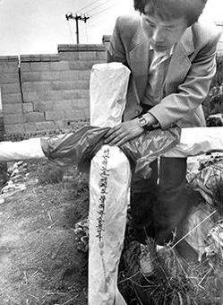 """1987년 5월 화성 연쇄살인 사건 피해자의 원혼을 달래기 위해 피해자의 가족들이 범행 장소에 세워둔 허수아비. 허수아비에는 범인에게 """"너는 어느 손에라도 잡혀 죽을 것이다"""" 라고 쓰여있다. /조선DB"""