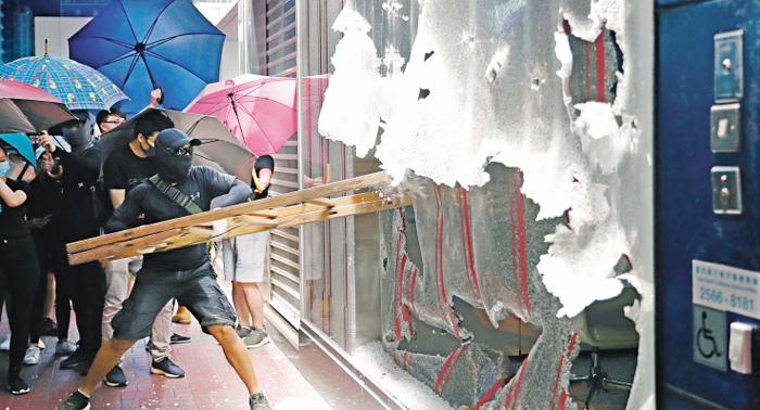 복면금지법에 반발… 홍콩 시위대, 중국계 은행·점포 공격 - 검은색 모자와 마스크 등을 착용한 홍콩 시위 참가자가 홍콩 몽콕 지역에서 지난 4일(현지 시각) 중국은행 몽콕 지점의 유리벽을 사다리로 깨부수고 있다. 홍콩 정부가 집회 때 마스크 착용을 금지하는 '복면금지법'을 시행한다고 4일 발표한 이후부터 이에 불복한 홍콩 시민들의 격렬한 시위가 6일까지 계속됐다. 일부 시위대는 중국 기업 점포와 중국인을 공격했다.