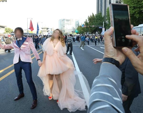 문재인 하야 범국민투쟁본부가 9일 오후 서울 광화문광장에서 개최한 '대한민국 바로세우기 국민대회' 를 마친 시민들이 청와대 방향으로 행진하는 동안 러시아 커플이 웨딩사진을 찍고 있다. /뉴시스