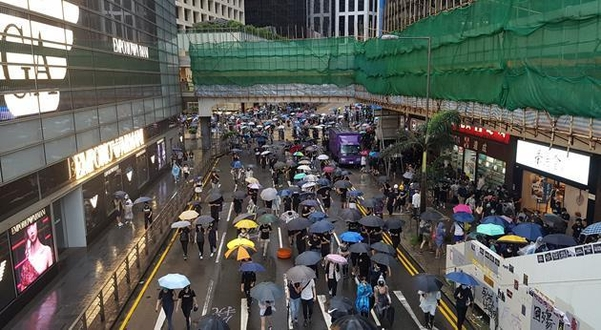 지난 6일 홍콩 시위대가 정부의 복면금지법 시행을 규탄하며 홍콩 도심을 행진하고 있다. 주변의 상점들은 장사가 되지 않아 일찍 문을 닫는 경우가 늘었다./ 연합뉴스