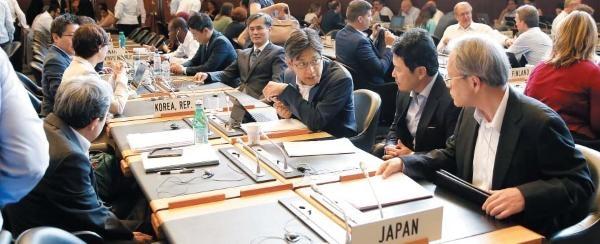 지난 7월 24일 스위스 제네바에 있는 WTO 본부 회의장에서 열린 일반이사회를 앞두고 일본 대표단이 이야기를 나누고 있다. 바로 옆에 한국 대표단이 앉아 있다. /로이터 연합뉴스