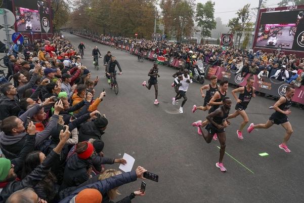 흰색 민소매를 입은 킵초게가 뛰고, 앞뒤에서 페이스메이커들이 같이 뛰어주거나 갈길을 레이저로 쏴주고 있다. /AP연합뉴스
