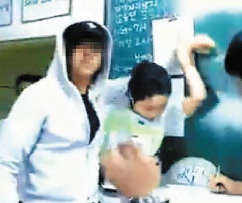 """서울의 한 고교 교실에서 남학생(왼쪽)이 수업을 마친 교사의 어깨에 손을 걸치며""""누나 사귀자""""라고 말하는 모습. 2009년 이 장면을 찍은 동영상이 인터넷에 올라와 지금도 검색되고 있다."""