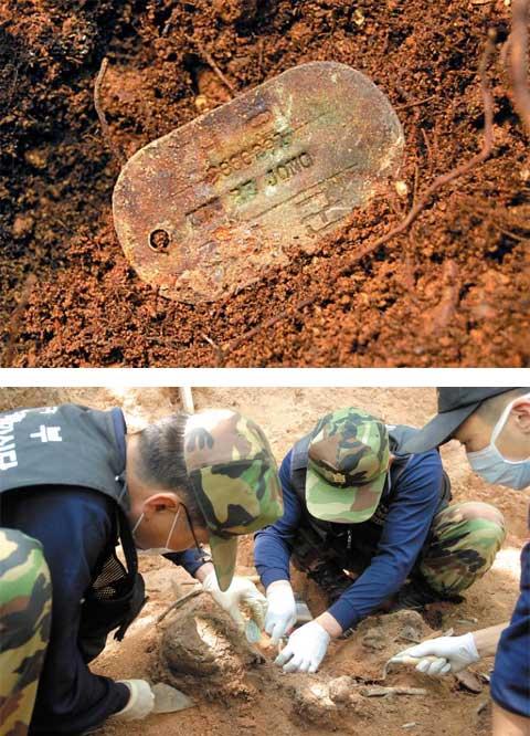 강원도 양구군 방산면 백석산 일대에서 수 시간 땅을 파던 병사들이 흙더미 아래서 발견한 인식표(군번줄) 하나. 6·25 당시 국군과 북한군 사이에 치열한 격전이 벌어진 백석산 일대에서는 수많은 유해가 발견되고 있다. 인식표는 유해 신원 확인의 가장 결정적인 증거가 된다. 흙 속에 묻혀있던 인식표(사진 위)와 발견된 유해를 수습하고 있는 유해 발굴 감식단원들(아래 사진). /유해발굴감식단 제공