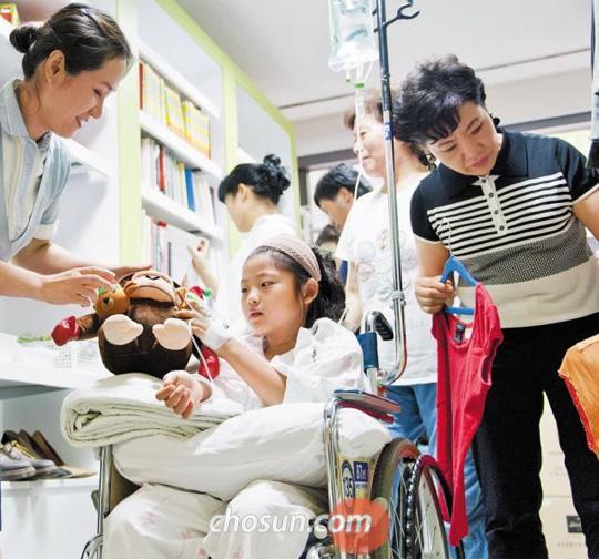 지난 19일 신촌세브란스병원 4층에 있는 자선 가게 '세·움'에서 환자와 그 가족이 물건을 고르고 있다. 팔을 다쳐 입원한 길모(10·가운데)양은 인형을, 길양의 엄마(오른쪽)는 옷을 골랐다. 판매 금액 중 절반은 암환자 치료비로, 나머지는 암환자 가족을 위한 여행비로 쓰인다. /김지호 객원기자 yaho@chosun.com