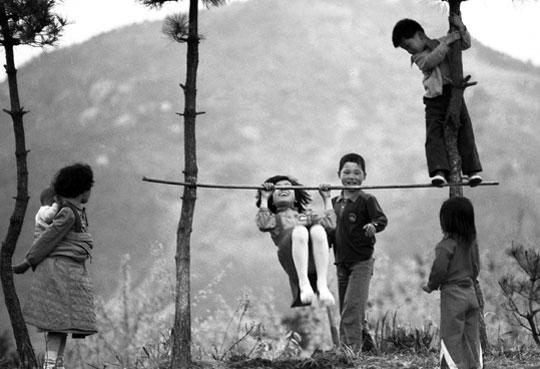 박신흥 이사가 1975년에 찍은'턱걸이'. 한 여자 아이가 오빠들이 하던 턱걸이를 안간힘을 쓰고 흉내 내고 있다.