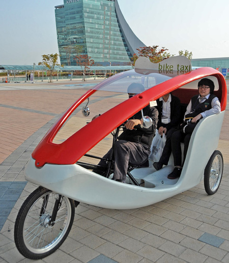일산 킨텍스의 명물로 등장한 자전거 택시(bike taxi). 페달과 전기 동력을 함께 사용하는 전기 자전거로 소음과 매연이 없어 친환경 교통수단으로도 각광을 받고 있다. 자전거 택시는 현재 킨텍스 전시장 구내이동과 투어에 활용되고 있다. /킨텍스 제공